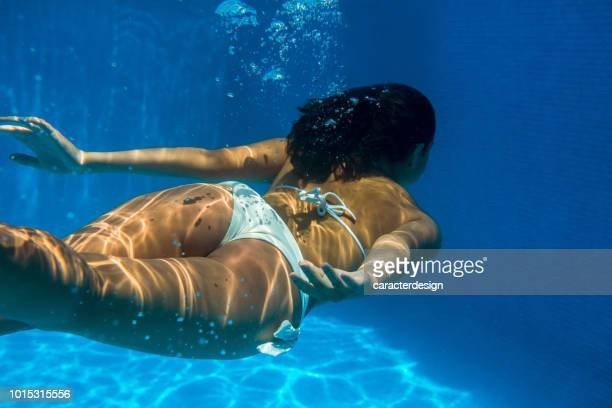 Girl underwater diving in a swimming pool