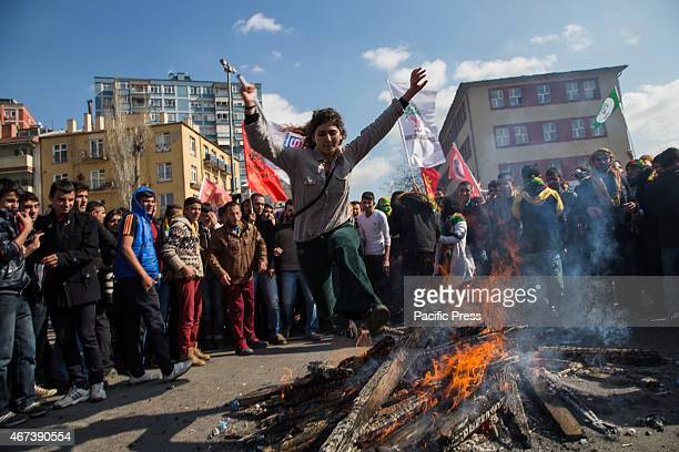 A girl unexpectedly jumps over the fire at Newroz celebration rally Traditionally only men jump the bonfire at Newroz but this year many girls joined...