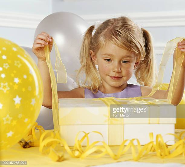 girl (3-5) untying yellow ribbon around present - long bright yellow dress stock pictures, royalty-free photos & images