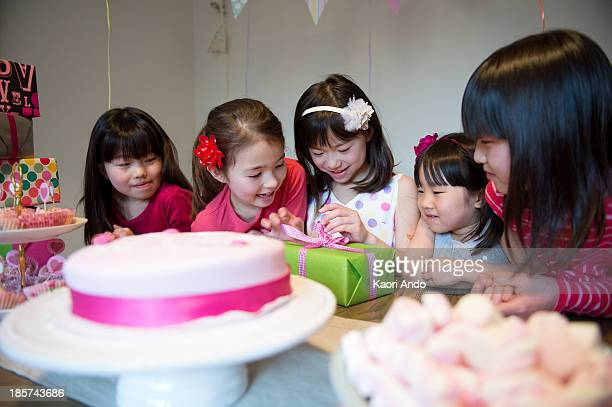 girl unwrapping birthday present at party - cobham surrey stock pictures, royalty-free photos & images