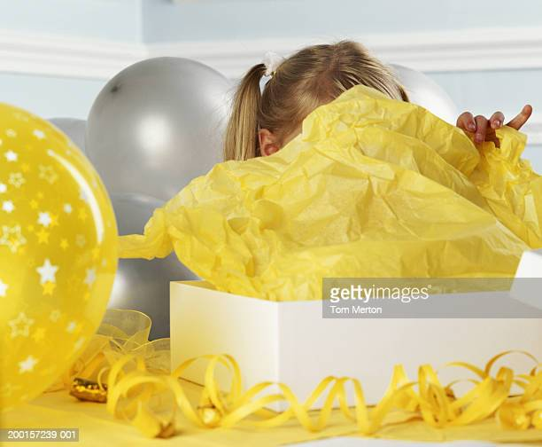 Girl (3-5) unwrapping present, face obscured by tissue paper