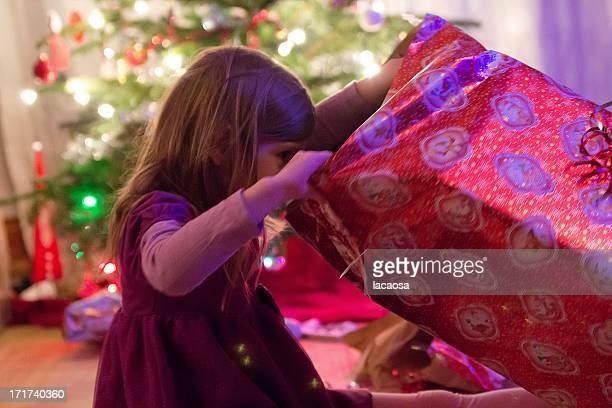 girl unwraps christmas gift