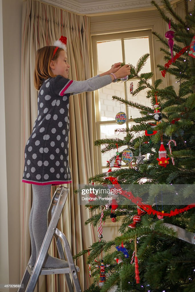 girl up a ladder decorating christmas tree stock photo