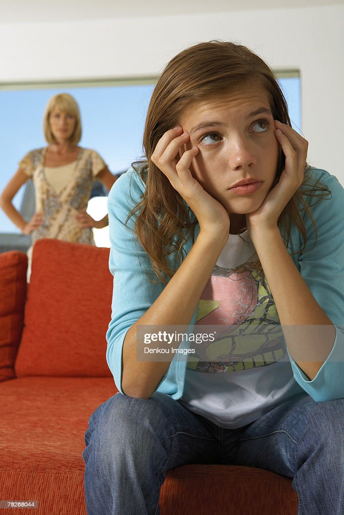 Girl upset, mother in the background. : Stock Photo