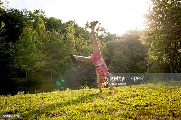 Girl upside down doing cartwheel looking at camera