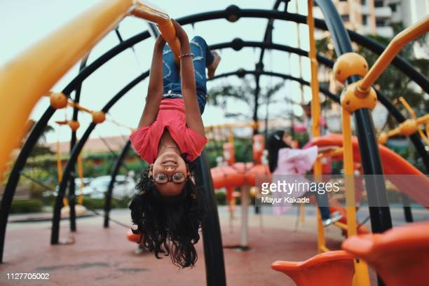 girl upside down on the jungle gym - playground stock pictures, royalty-free photos & images
