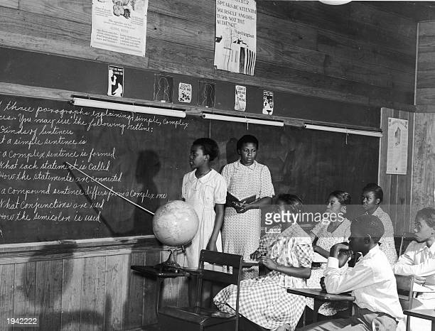 A girl uses a pointer to read sentences from a classroom blackboard while a teacher and other students look on circa 1940