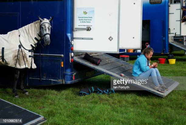 A girl uses her phone as she sits on the ramp of her trailer during 152nd the Ryedale Country Show on July 31 2018 in Kirbymoorside England Held in...