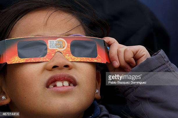 A girl uses special glasses to look into the sky during a partial solar eclipse outside the Planetario on March 20 2015 in Madrid Spain In Madrid the...