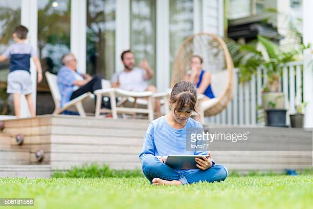Mädchen mit einem Tablet PC auf dem Rasen