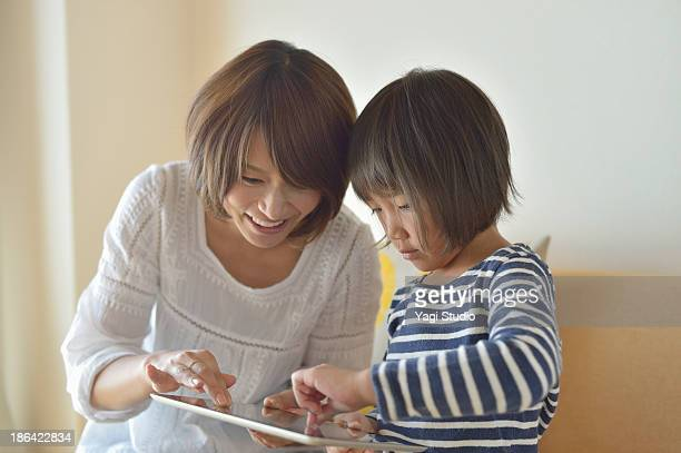Girl using a digital tablet with Mother