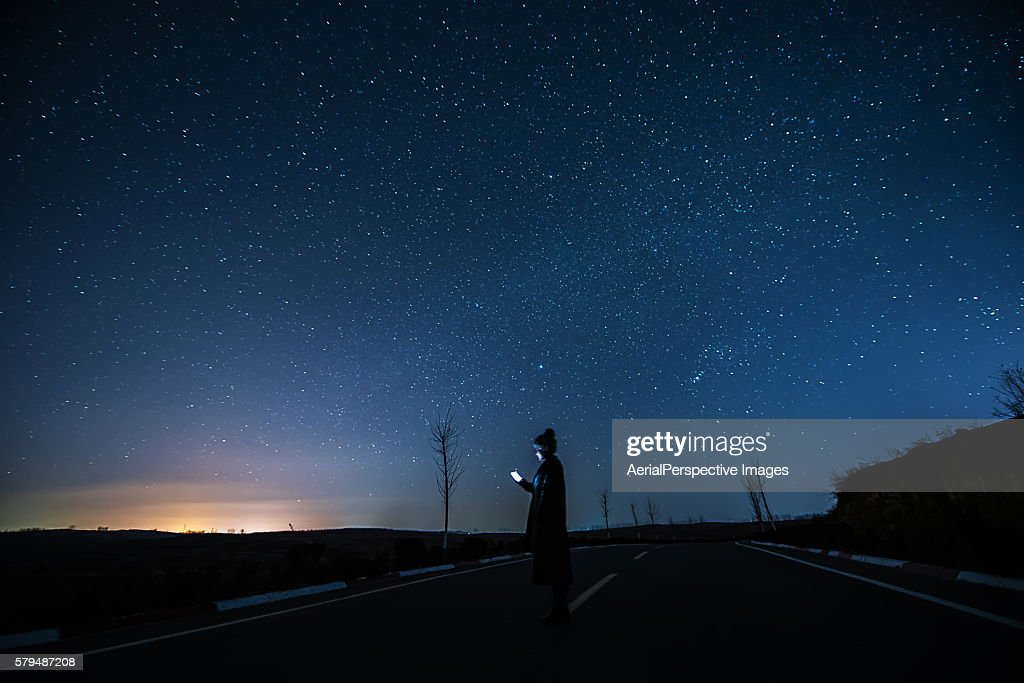 Girl Using A Mobile Phone in Starry night : Stock Photo