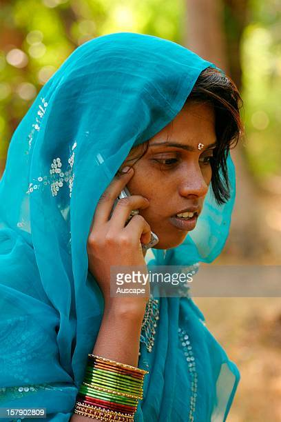 Girl using a mobile phone. India is a world leader in telecommunications and other technologies, which exist alongside traditional values. Goa, India.