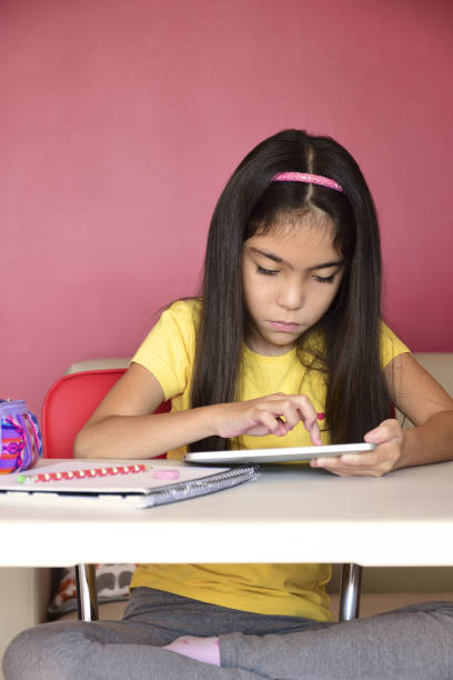 Girl using a tablet to do her homework