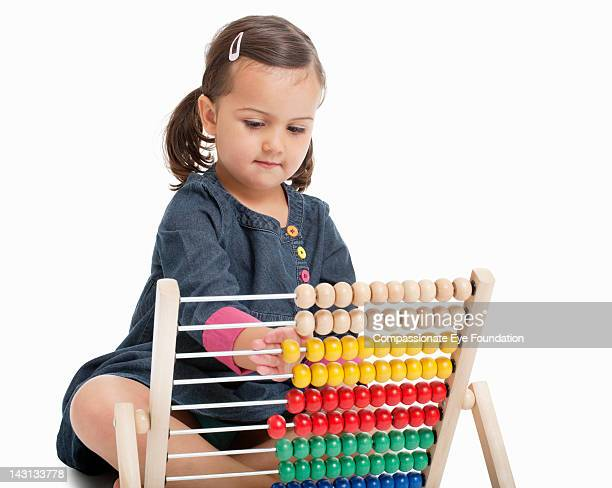 """girl (3-4) using abacus, studio shot - """"compassionate eye"""" stock pictures, royalty-free photos & images"""
