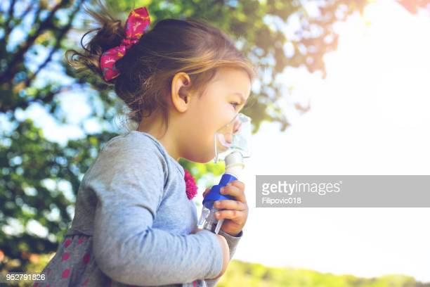 Girl using asthma inhaler in a park