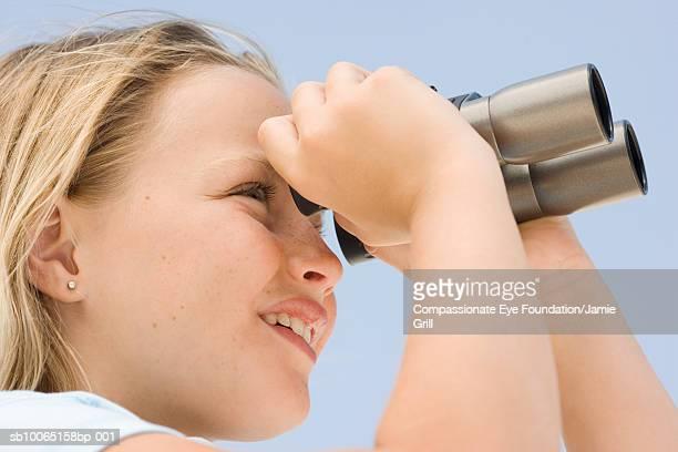 Girl (8-9) using binoculars, close-up