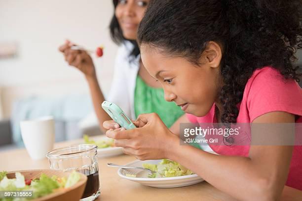 Girl using cell phone at dinner
