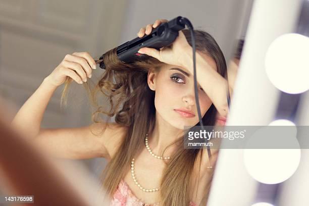 girl using curling iron