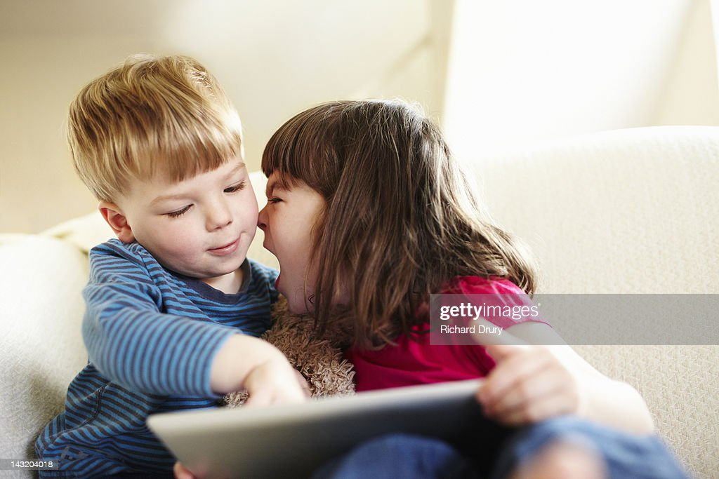 Girl using digital tablet and shouting at brother : Stock Photo