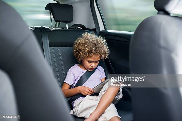 Girl using digital tablet in car
