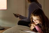 Girl using digital tablet on bed