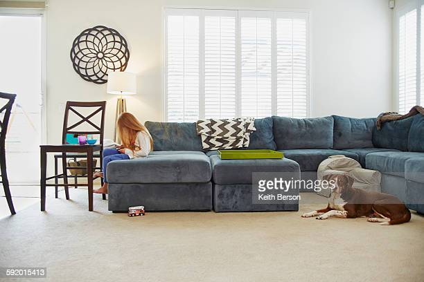 Girl using digital tablet on sofa in living room, dog behind her