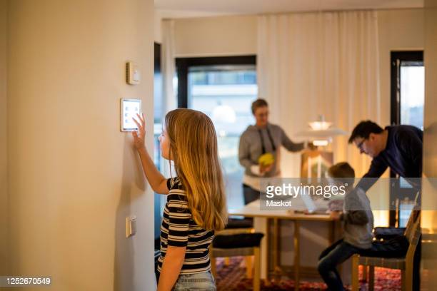 girl using digital tablet on wall with family in background at smart home - internet delle cose foto e immagini stock