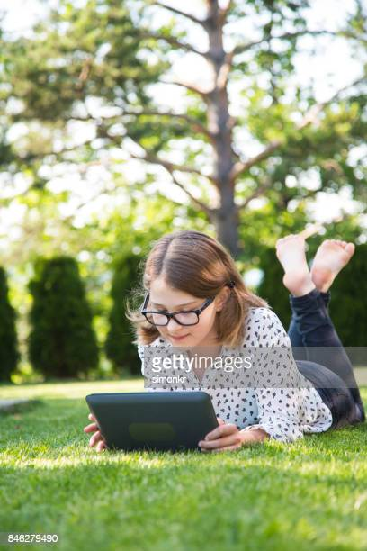 girl using digital tablet - 13 years old girl in jeans stock photos and pictures