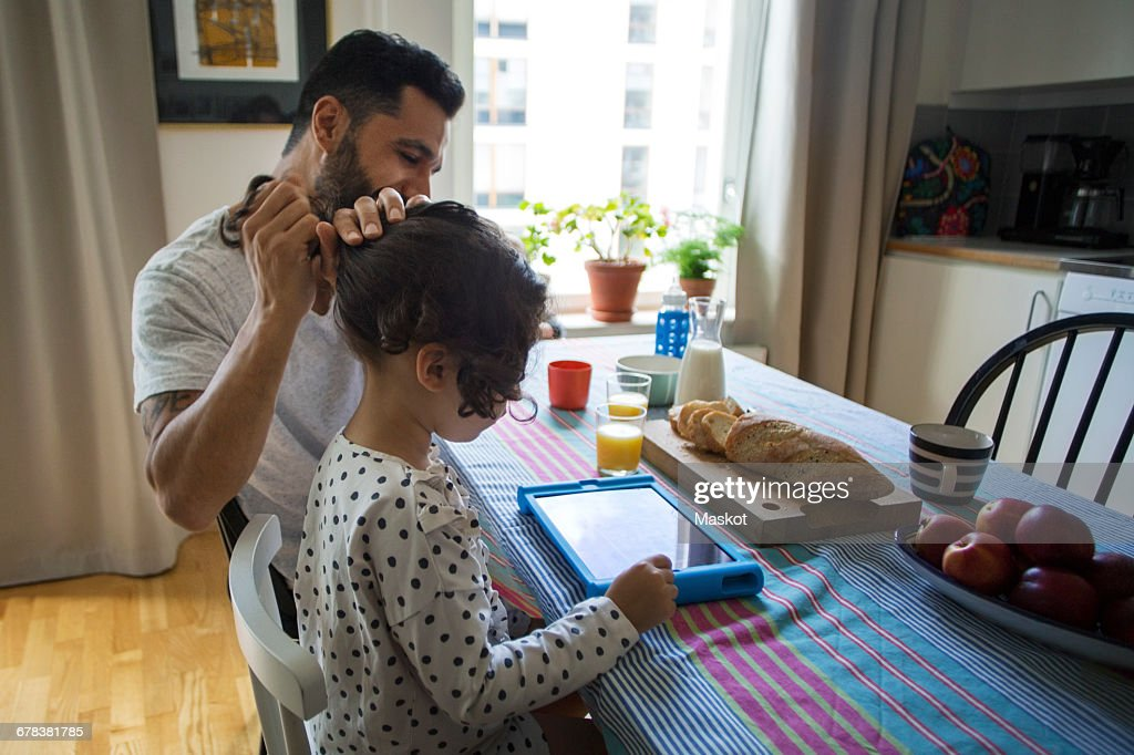 Girl using digital tablet while father tying her hair at table