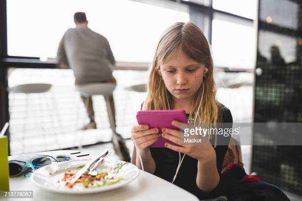 Girl using digital tablet while sitting at table in restaurant