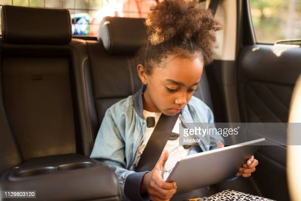 girl using digital tablet while sitting in electric car - alternative fuel vehicle stock pictures, royalty-free photos & images