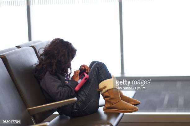 Girl Using Digital Tablet While Sitting On Bench