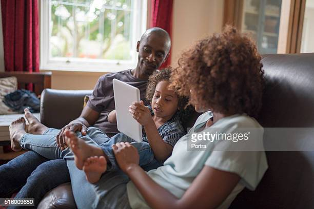Girl using digital tablet while sitting with parents on sofa