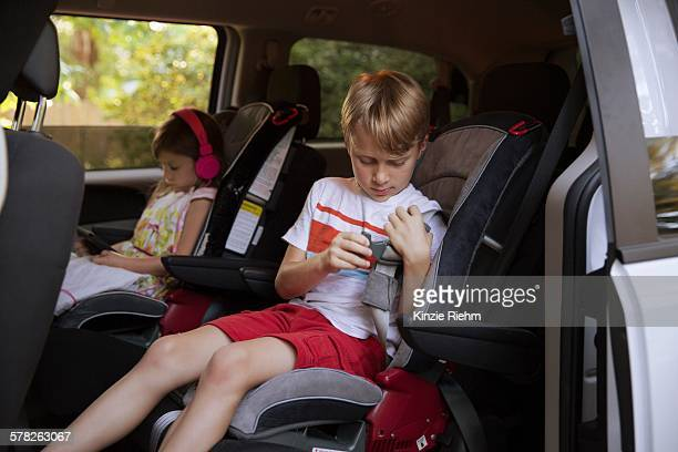 Girl using digital tablet whilst brother fastens seat belt in car back seat