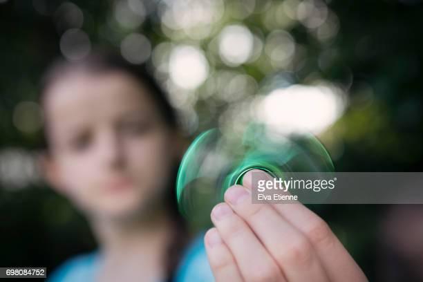 Girl (12-13) using fidget spinner