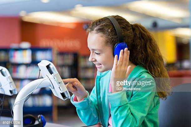 Girl using headphones and tablet to listen to library audiobook