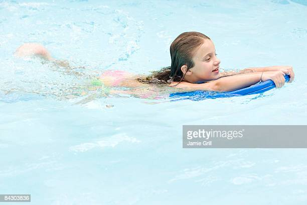 Girl using kickboard in swimming pool