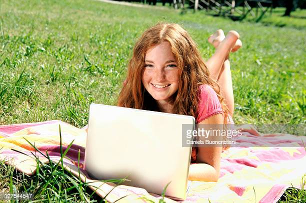 girl using laptop on grass - barefoot redhead stock photos and pictures