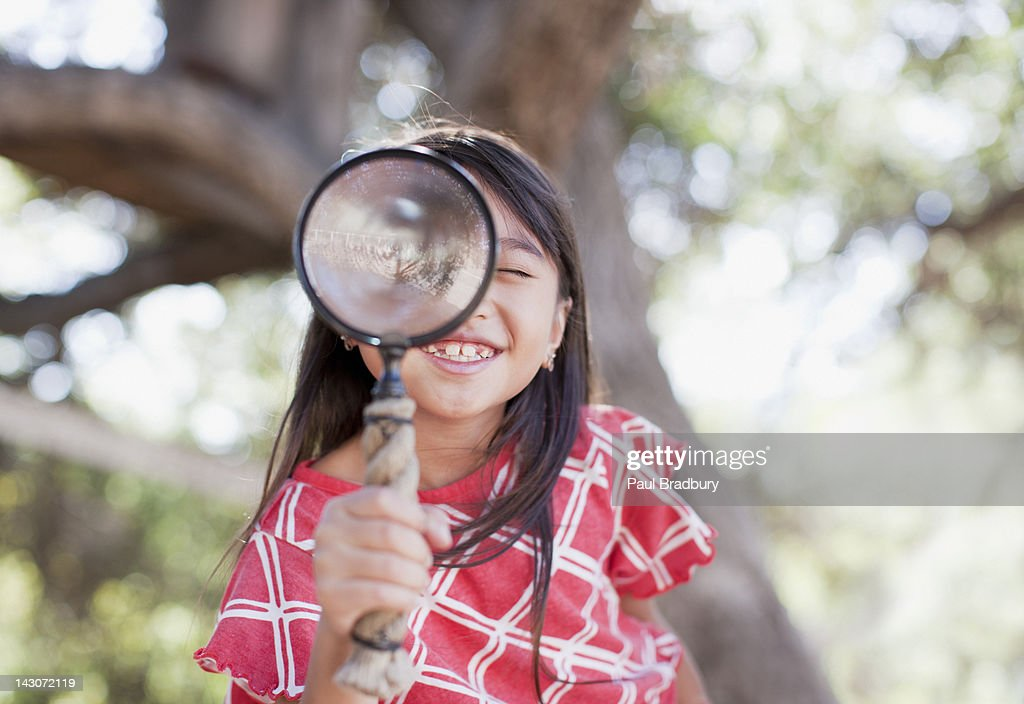 Girl using magnifying glass outdoors : Stock Photo