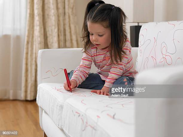 girl using marker on sofa - vernieling stockfoto's en -beelden