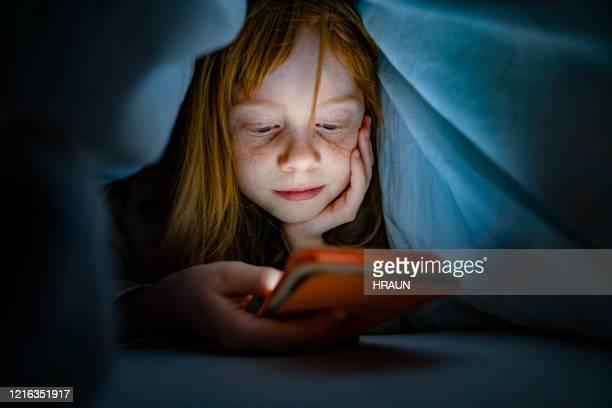 暗闇の中でベッドで携帯電話を使用して女の子 - 少女一人 ストックフォトと画像