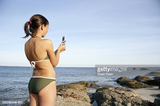 girl (10-12) using mobile phone on beach, rear view - 10 11 years stock photos and pictures