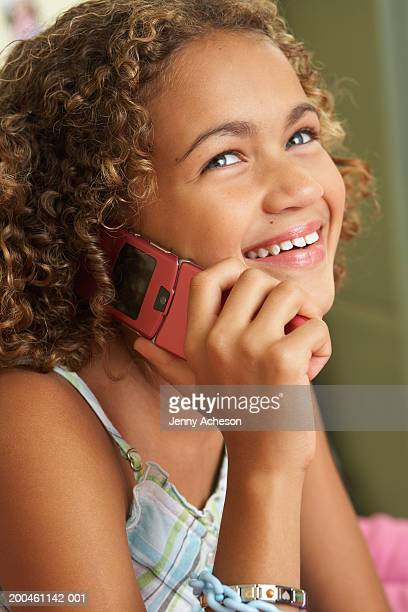 Girl (11-13) using mobile phone, smiling, close-up