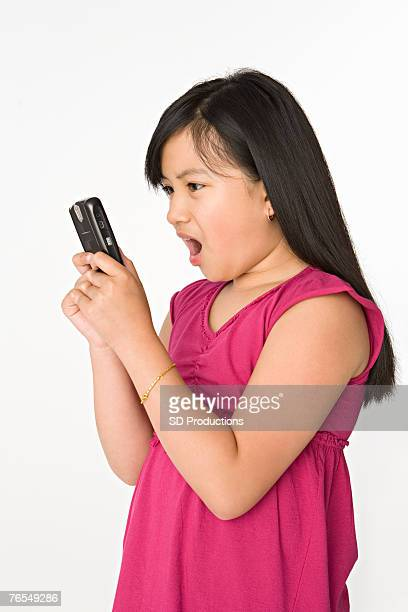 girl (10-11 years) using mobile phone, studio shot - 10 11 years stock pictures, royalty-free photos & images