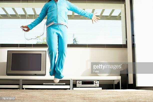 Girl Using Mp3 Player and Jumping in Living Room