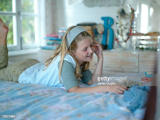 Girl (8-10) using on phone on bed