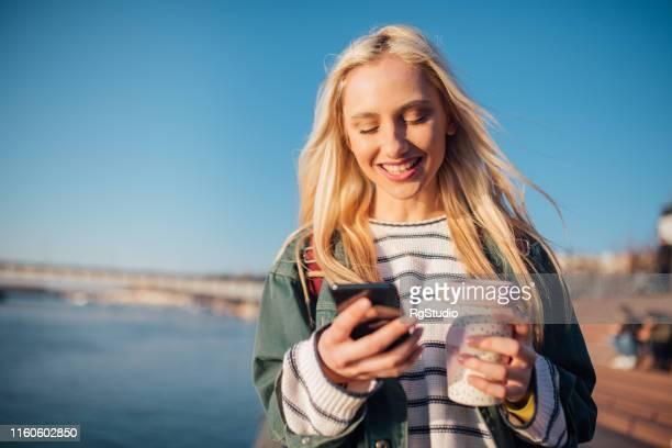 mädchen mit telefon - blond frauen strand stock-fotos und bilder
