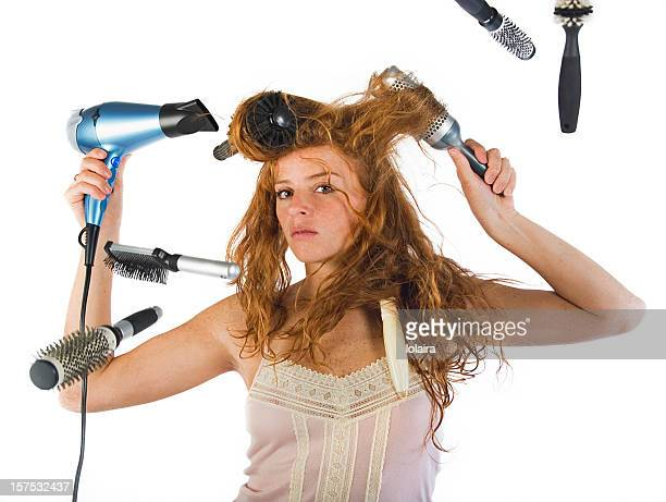 Girl using six brushes and a hair dryer to style her hair