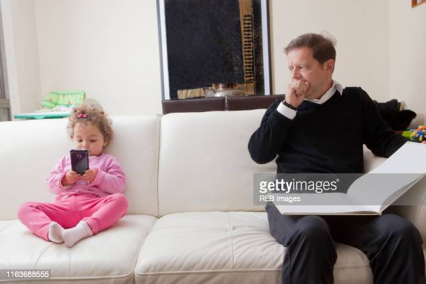 girl using smart phone as her father reads book - generation gap stock pictures, royalty-free photos & images